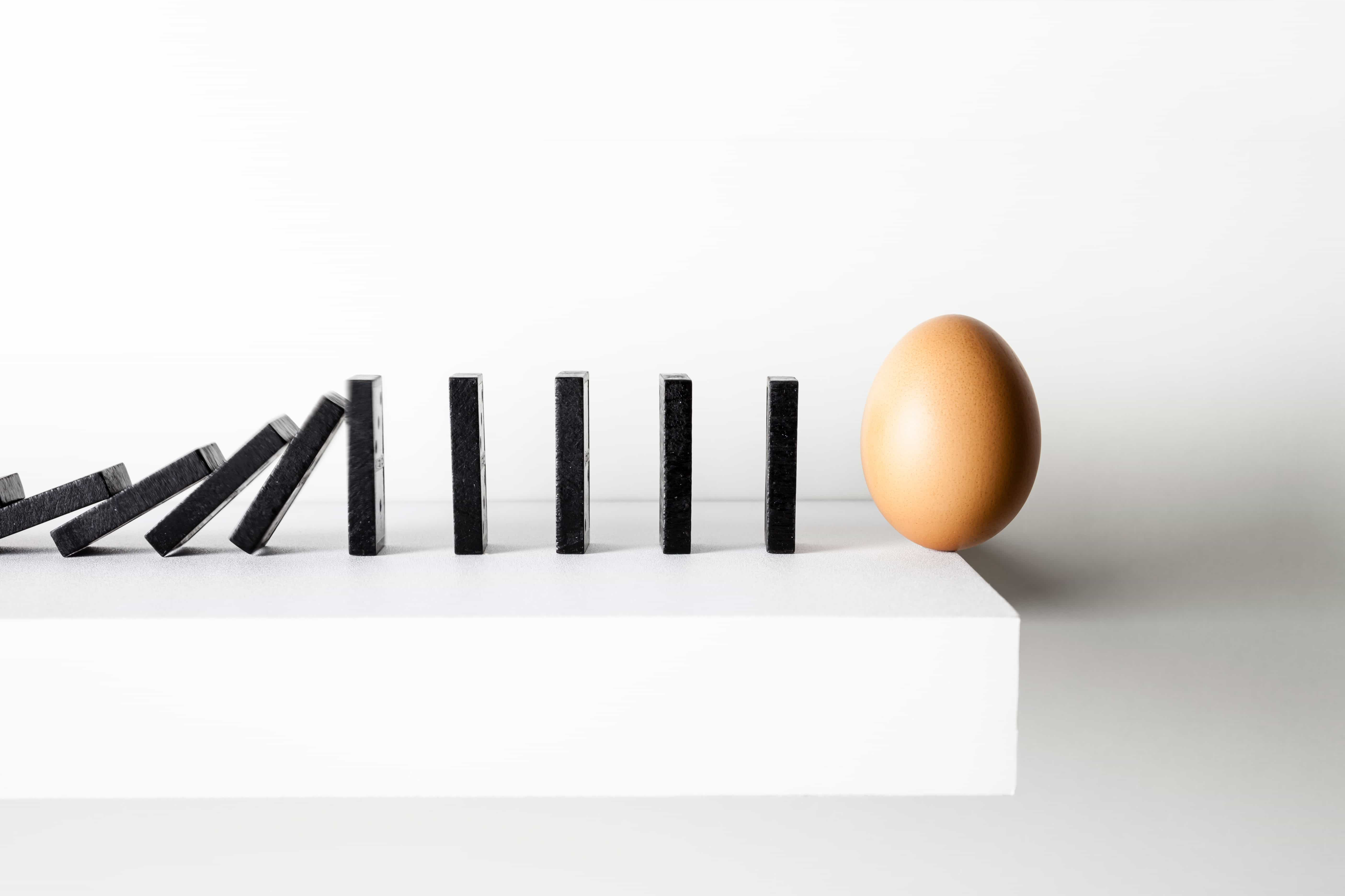 Dominoes on a shelf leading to an egg balanced precariously on the edge